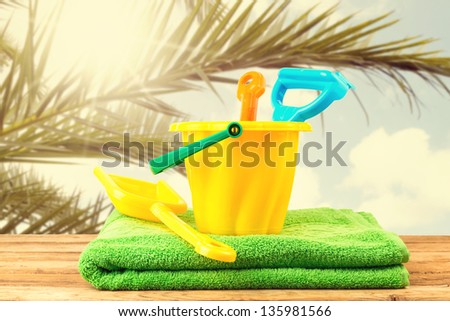 Beach items on wooden deck over palm tree branches - stock photo