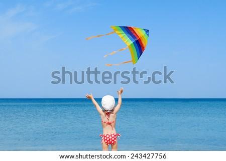 beach kid girl kite flying outdoor coast shore unrecognizable - stock photo
