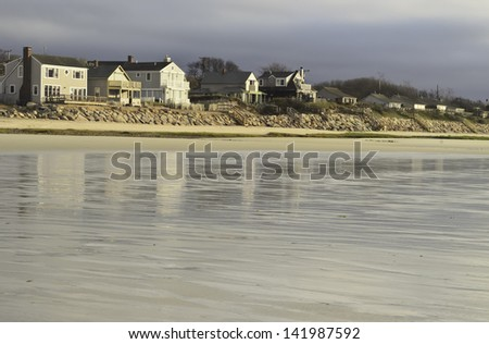 Beach landscape with long retaining wall near sunset across reflective tidal flats of Brewster, Massachusetts - stock photo