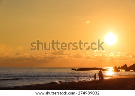 Beach landscape with silhouette of mother with her daughter and baby, pushing a stroller on a sandy beach in late summer, enjoying the evening chill. Family vacation, traveling with children concept.  - stock photo