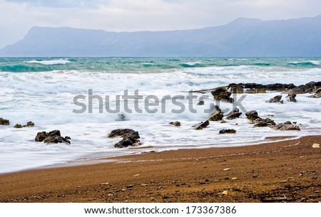 Beach landscape with stormy foamy waves crushing on the rocks - stock photo