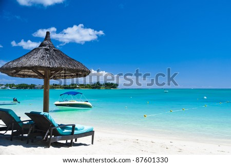 Beach lounge chairs on the exotic tropical island of Mauritius - stock photo