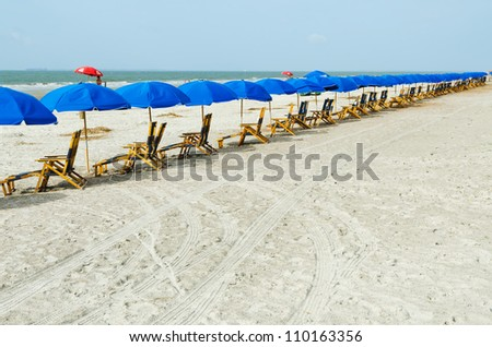 Beach lounge chairs with umbrellas. South Carolina Atlantic coast. - stock photo