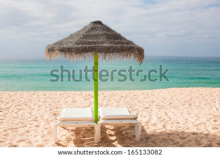 Beach loungers and umbrellas on the exotic resort at desert coast - stock photo
