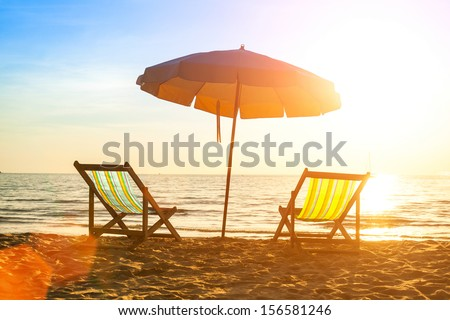 Beach loungers on deserted coast sea at sunrise. - stock photo