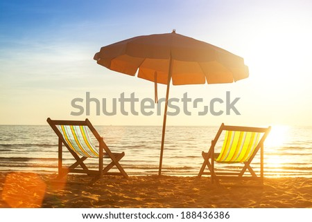Beach loungers on deserted coast sea at sunrise.