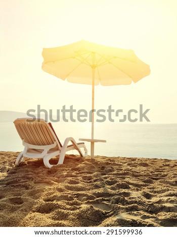 Beach loungers on deserted coast sea at sunrise - stock photo