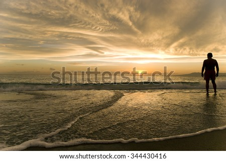 Beach Man silhouette is a silhouette of a man standing in triumph and exaltation as the beautiful surreal sunset fills the cloudscape sky. - stock photo