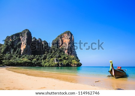 beach mountains and long tail boat in thailand - stock photo