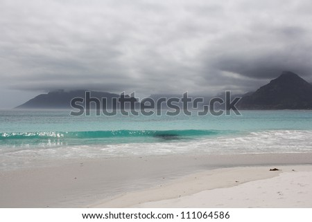 Beach of Kommetjie with an upcoming storm in the background and blue water