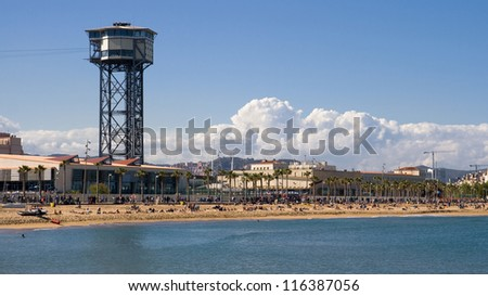 Beach of San Sebastia with the cable car tower of the port of Barcelona, Catalonia.