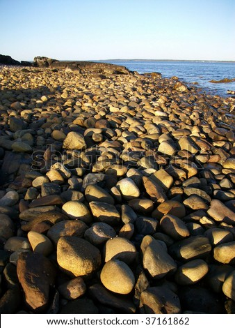 Beach of stones along Penobscot Bay, Lincolnville, ME. - stock photo