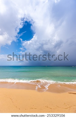 Beach on the tropical island. Clear blue water, sand and clouds. Beautiful vacation spot. - stock photo