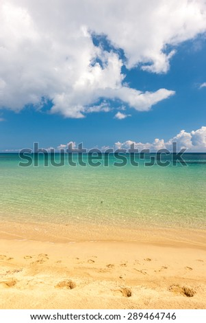 Beach on the tropical island. Clear blue water, sand and clouds. Beautiful vacation spot.