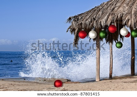 Beach Palapa Decorated For Christmas Season ~ Red, White and Green Ornaments ~ Splashing Waves - stock photo