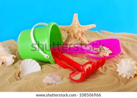 beach plastic toys-bucket,spade and rake lying on the sand with seashells - stock photo