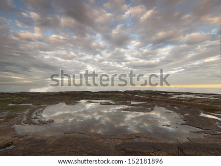 Beach reflections in a rock pool - stock photo
