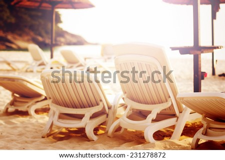 Beach relaxation concept. Row of beach chairs on the sunshine coastline. Image toned in warm colors. Vintage color effect. - stock photo