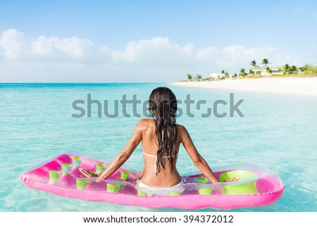 Beach relaxation woman floating on pink inflatable air bed pool mattress toy float in ocean beach background in pristine blue turquoise water at luxury caribbean getaway resort. - stock photo