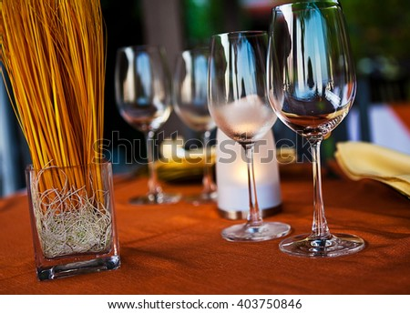 Beach restaurant with sea view, table with empty wine glasses, plates - stock photo