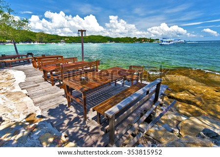 Beach restaurant wooden tables in the border of sea, textured stones of the coastline is at foreground, and eastern coastline of Ko Samet island is at background, Thailand - stock photo