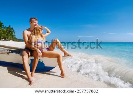 Beach romantic couple looking. Happy young couple sitting on boat under sunny summer sun.Travel holidays concept. - stock photo