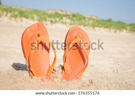 BEACH SANDALS IN SAND Orange flip flops in beach sand in front of dunes.
