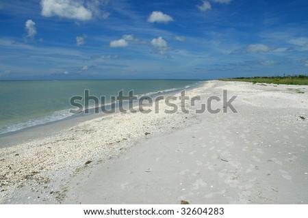 Beach scene with sky, sand and ocean - stock photo