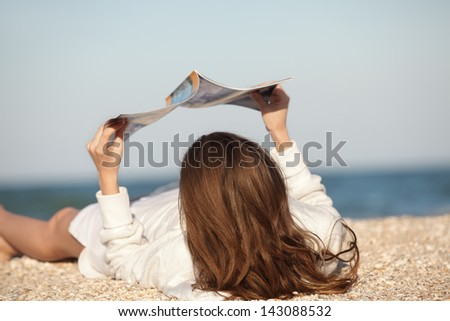 Beach scene. Young woman reading magazine - stock photo