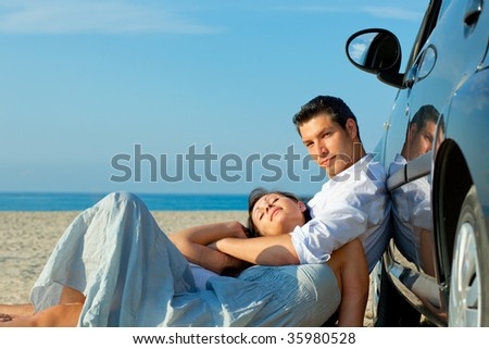 Beach sea coastline lying together masculine and feminine pair of to young adults driver loving embracing and the togetherness being in love - stock photo