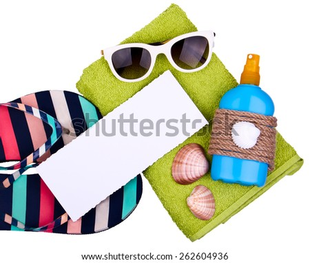 Beach set - Green towel, slippers with color stripes, white sunglasses and suntan lotion on white background, isolated. Blue bottle of lotion decorated with rope and shell. Paper card for your text. - stock photo