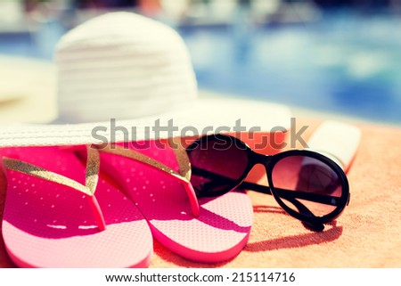 beach, summer and vacation concept - close up of hat, flip-flops, sunscreen and sunglasses at pool - stock photo