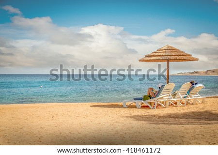 Beach: summer beach with lovers couple on a beach with sandy beach, blue sky and white cloud and ocean, umbrella beach for beach plain relaxing and sun shine beach on a beach for beach background. - stock photo