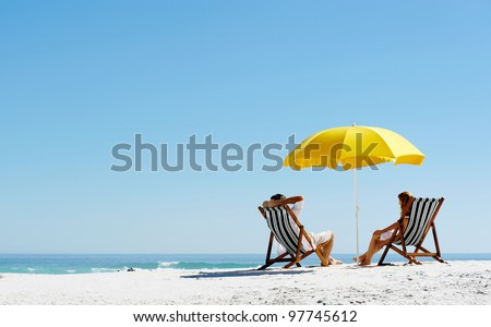 Beach summer couple on island vacation holiday relax in the sun on their deck chairs under a yellow umbrella. Idyllic travel background. - stock photo