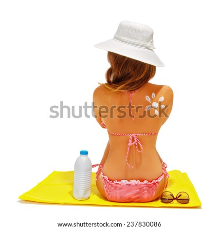 Beach summer holidays. Woman wearing red bikini and beach hat sitting on the mat. Concept of sun protection, model with sunscreen and sunglasses. Isolated, over white, with copy space.  - stock photo