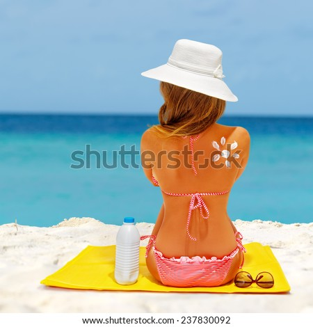Beach summer holidays. Woman wearing red bikini and beach hat sitting on the mat. Concept of sun protection, model with sunscreen and sunglasses.  - stock photo