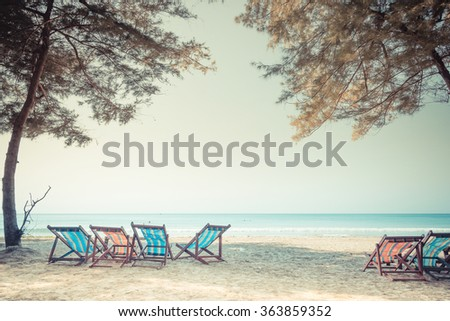 Beach summer on island vacation holiday relax in the sun on their deck chairs under a giant tree. Idyllic travel background. Vacation Sunset Concept - Vintage retro picture style. - stock photo