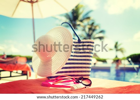 beach, summer vacation and accessories concept - close up of hat, bag, sunscreen and sunglasses at pool - stock photo