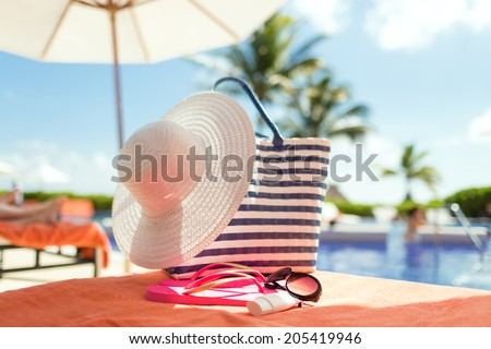 beach, summer, vacation and accessories concept - close up of hat, flip-flops, bag, sunscreen and sunglasses at pool - stock photo