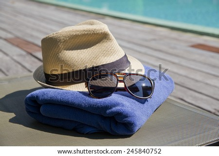 beach, summer, vacation and accessories concept - close up of hat, towel and sunglasses at pool - stock photo