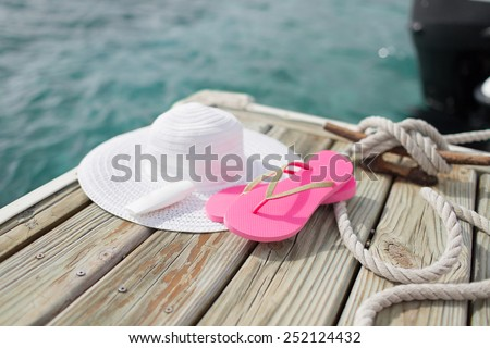beach, summer, vacations and accessories concept - close up of hat, sunscreen and slippers at seaside - stock photo