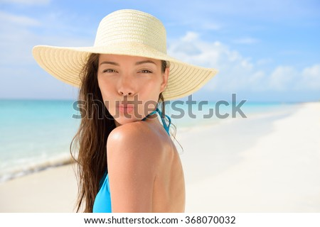 Beach sun hat woman blowing cute kiss on vacation. Asian female young adult model striking a kissing pose to the camera for summer holidays wearing straw sunhat and blue bikini on perfect white sand. - stock photo