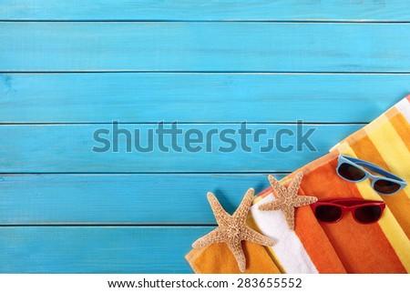 Beach sunbathing background, sunglasses, blue wood deck, copy space - stock photo