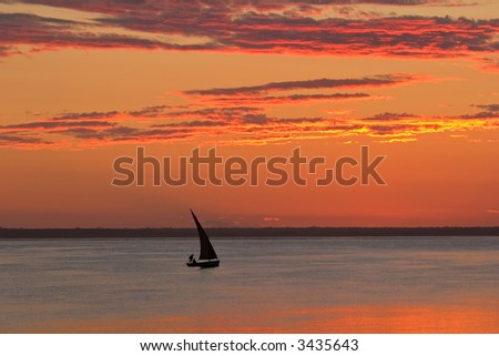Beach sunset scene in Mozambique with small sailboat (called a dhow)  - stock photo
