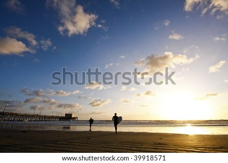 beach sunset with surfers and pier - stock photo