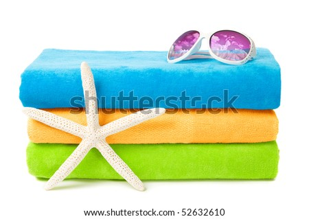 Beach towels with sunglasses and starfish on white background, summer sky reflected in the glasses - stock photo