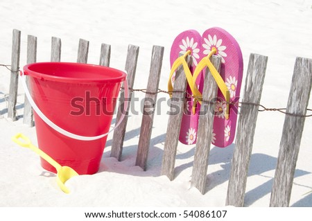 beach toy and shoes by sand dune fence - stock photo