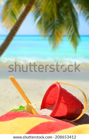 Beach toys and towel in red and yellow in  sand on a tropical Caribbean beach with palm tree and blue ocean in the background       - stock photo