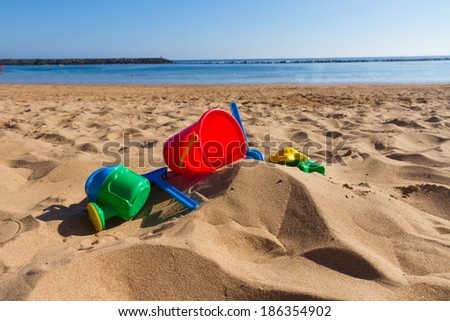 beach toys in sand on sea shore at sunny summer day - stock photo