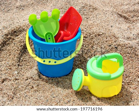Beach toys on sandy background , with watering can